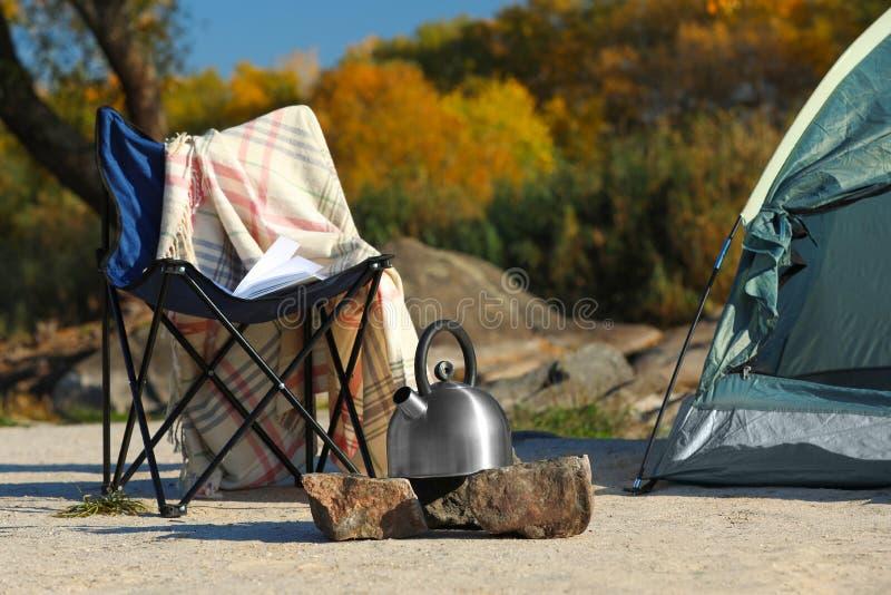Caldera de la silla y del metal cerca de la tienda de campaña fotos de archivo libres de regalías