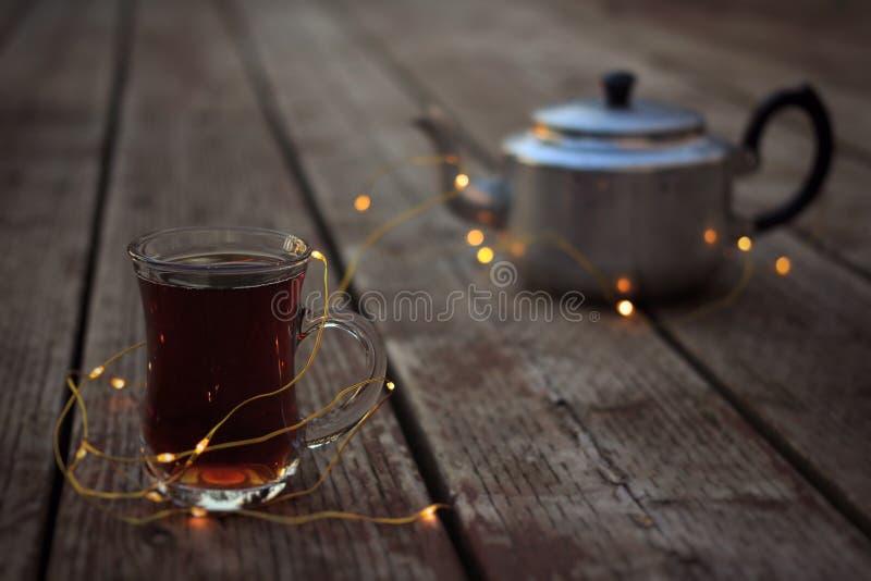 Caldera de té antigua y taza del vidrio de té caliente rodeada por las luces imagenes de archivo