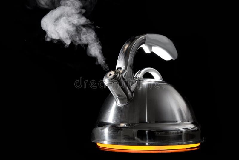 Caldera de té con el agua hirvienda foto de archivo