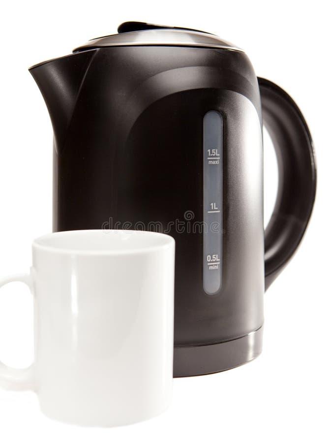 Caldera de té eléctrica plástica negra en un fondo blanco y una taza fotografía de archivo libre de regalías