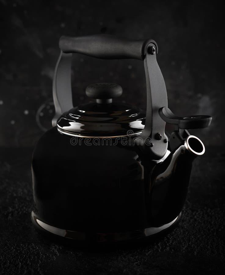 Caldera de té negro tradicional con el silbido en el fondo oscuro imagen de archivo