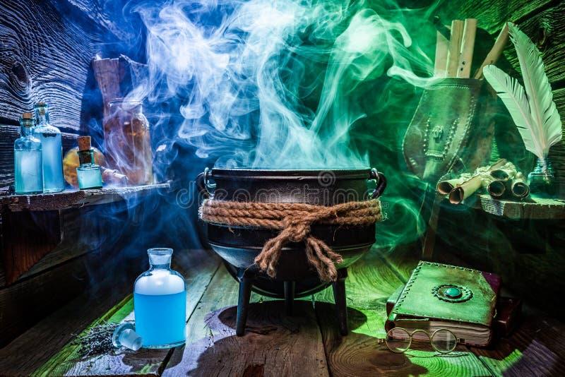 Caldera de Witcher con las pociones mágicas y los libros para Halloween foto de archivo libre de regalías