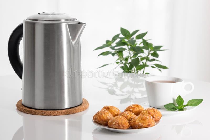 Caldera, taza de té y galletas eléctricas imágenes de archivo libres de regalías