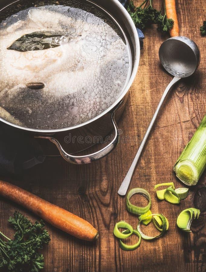 Caldo com a galinha fervida inteira em cozinhar o potenciômetro com ingredientes e concha na mesa de cozinha imagens de stock