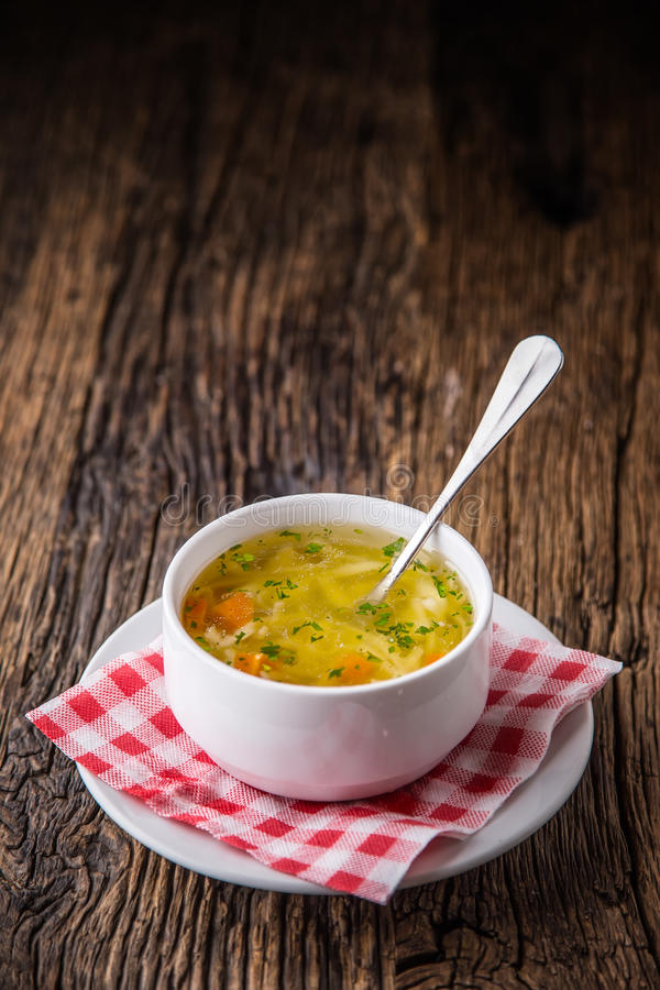 Caldo de galinha Caldo de carne Desosse o caldo com macarronetes cenoura e salsa na bacia branca foto de stock royalty free