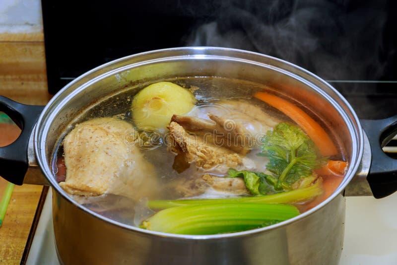 Caldo de galinha com partes de vegetais em um potenciômetro do metal antes de cozinhar com canja de galinha com os vegetais no pr fotos de stock
