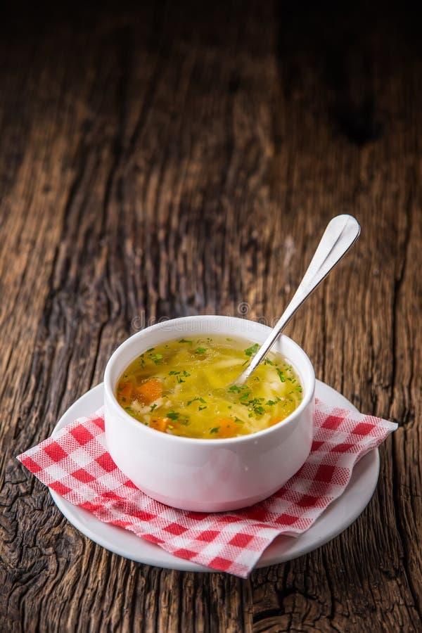 Caldo de pollo Caldo de carne de vaca Deshuese el caldo con los tallarines zanahoria y perejil en el cuenco blanco foto de archivo libre de regalías