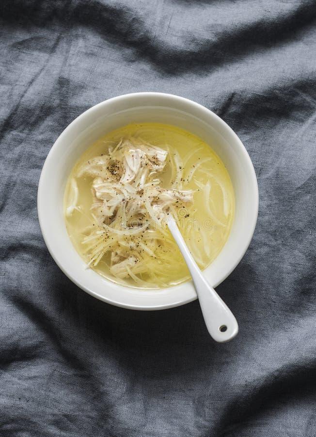 Caldo de pollo fácil con la carne, la cebolla y la pimienta del pollo Base de sopa en un fondo gris imagen de archivo