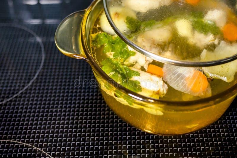 Caldo dietético saudável com os vegetais e a galinha cozinhados na caçarola de vidro transparente imagens de stock