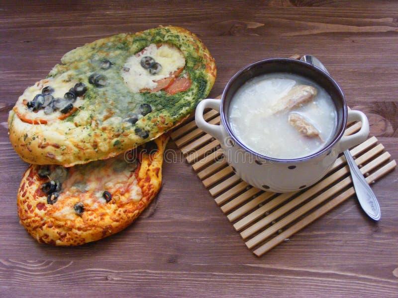 Caldo ruso tradicional del pollo en cuenco en la tabla de madera con la pizza hecha en casa de la corteza de la coliflor del vega fotografía de archivo libre de regalías