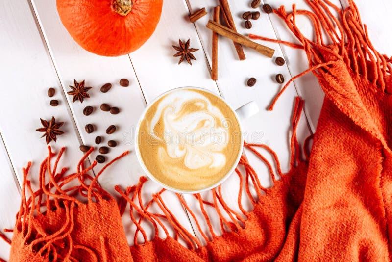 Caldo tricotti la sciarpa e la tazza di caffè caldo con schiuma Zucca arancio di Halloween, spezie e l'altra decorazione di festa fotografie stock