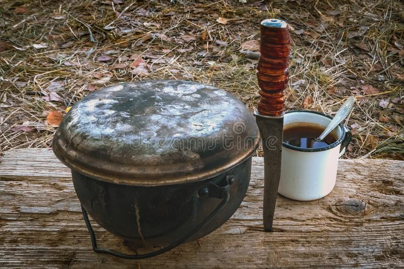 A caldron, a knife and a mug on a wooden stand in outdoor. Hiking set stock images