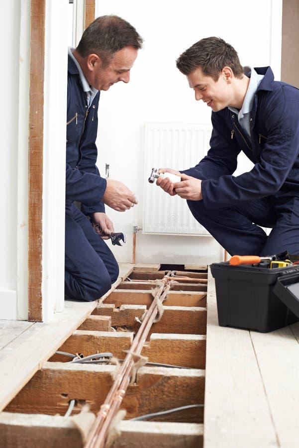 Calefacción central de And Apprentice Fitting del fontanero en casa imagen de archivo libre de regalías