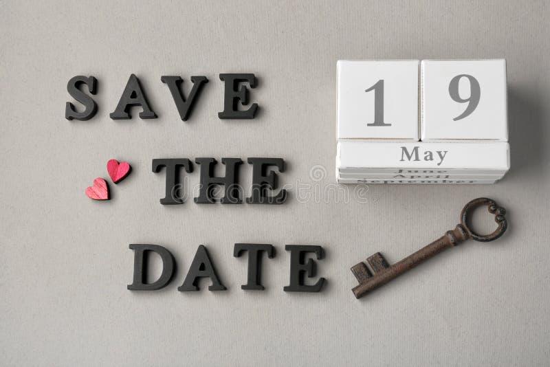 Calendário, chave do vintage e frase SALVO A DATA composta com letras no fundo cinzento imagem de stock