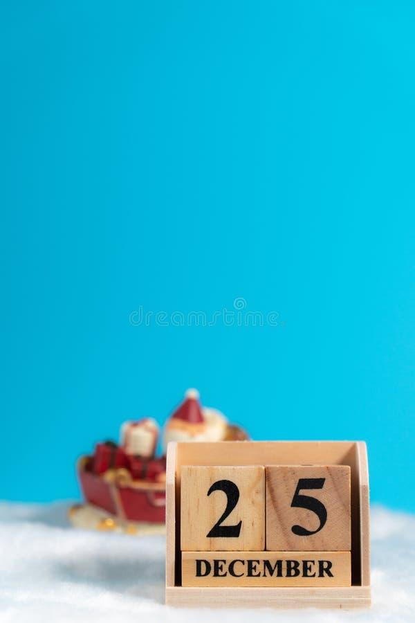 Calendário de bloco de madeira ajustado Natal data o 25 de dezembro na frente de Santa Claus com o 'trotinette' nas lãs brancas e fotografia de stock royalty free