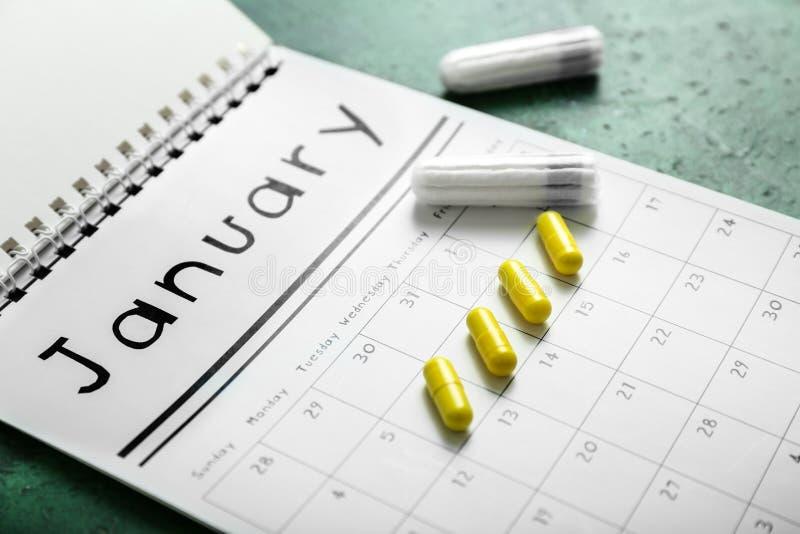 Calendário menstrual com comprimidos e tampões na tabela de cor foto de stock royalty free