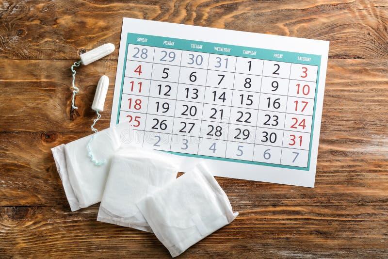 Calendário menstrual com os produtos femininos no fundo de madeira fotos de stock
