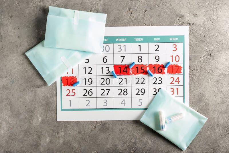 Calendário menstrual com produtos femininos e comprimidos no fundo cinzento imagens de stock royalty free
