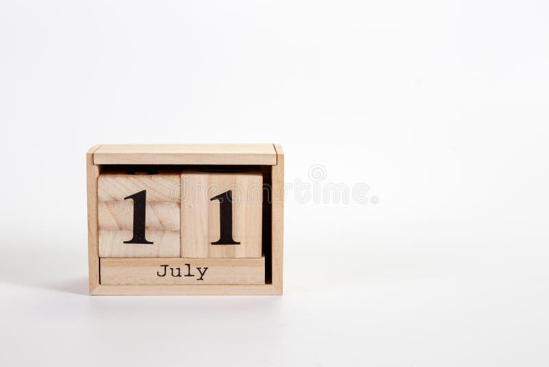 Calendário o 11 de julho de madeira em um fundo branco fotos de stock royalty free