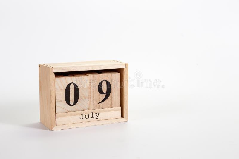 Calendário o 9 de julho de madeira em um fundo branco fotografia de stock royalty free