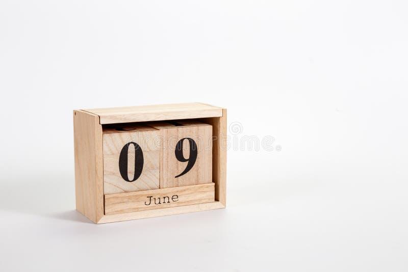 Calendário o 9 de junho de madeira em um fundo branco imagem de stock