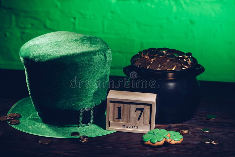 calendar, cookies in shape of shamrock, green irish hat and pot with golden coins on wooden vector illustration