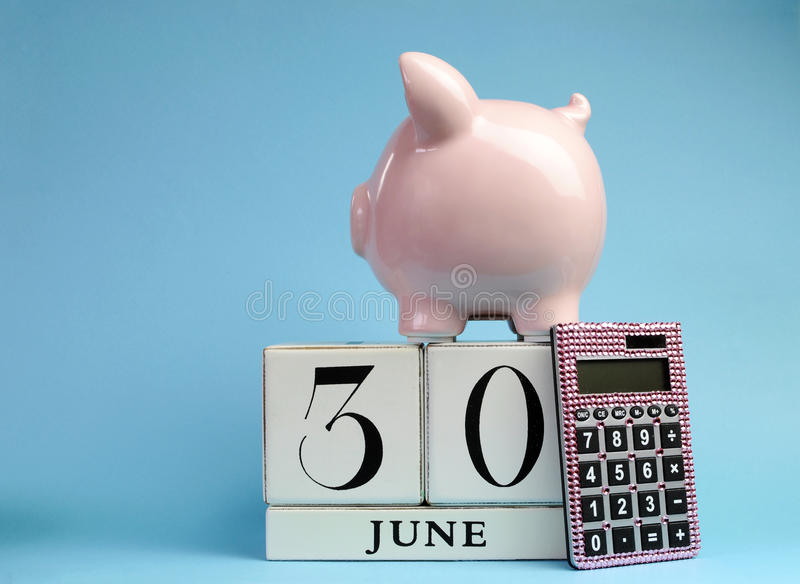 Calendar date for End of Financial Year, 30 June, for Australian tax year or retail stocktake sales. With piggy bank and pink calculator on sky blue background royalty free stock photos