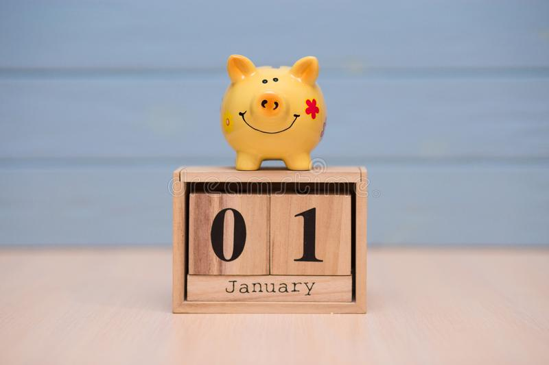 Calendar date of Financial Year start, 1st january with piggy bank on blue background. Winter time. New year concept royalty free stock image