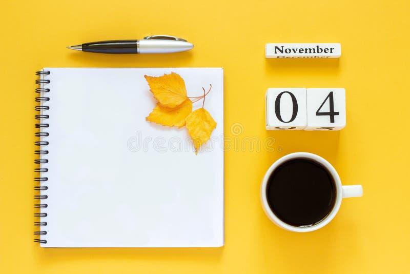 Calendar den November 04 koppen kaffe, notepad med pennan och gulna bladet på gul bakgrund arkivbild