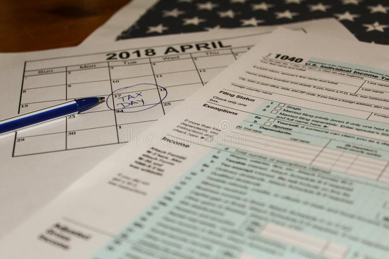 Calendar and form 1040 income tax form for 2017 showing tax day for filing is April 17 2018 royalty free stock photo