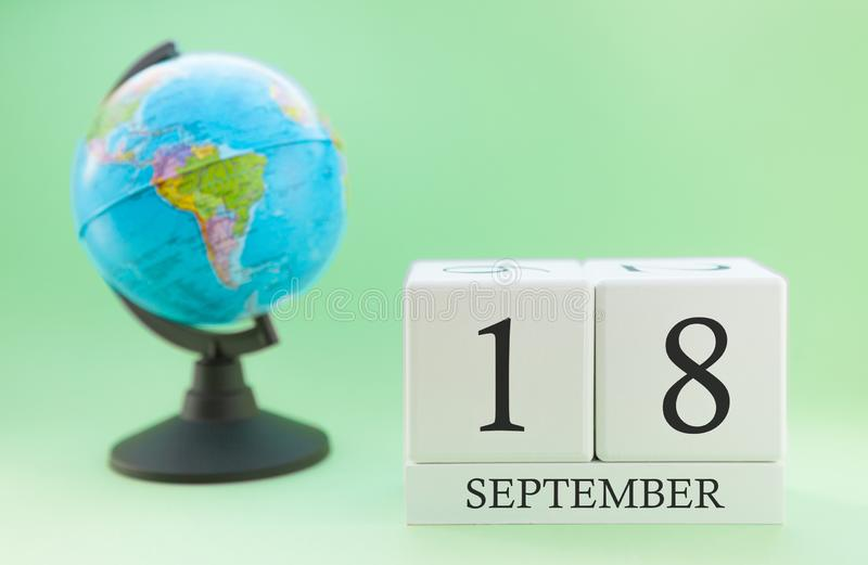 Calendar made of wood on a light green background, 18 day of the month September, autumn 18th day stock photo