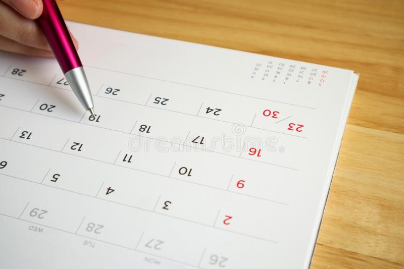 Calendar page with female hand holding pen on table stock photos