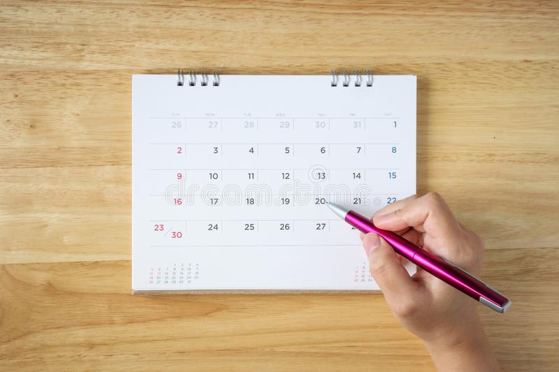 Calendar page on table with female hand holding pen royalty free stock image