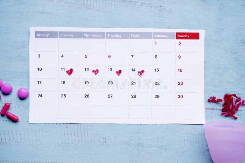 Calendar and pills with dirty sanitary cup royalty free stock photo