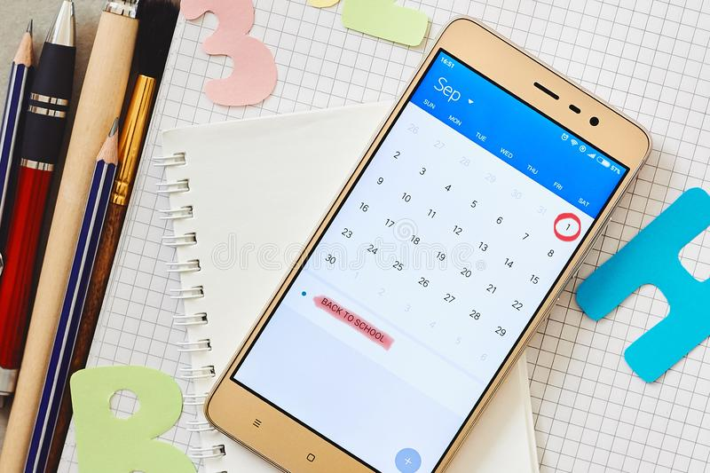 Calendar on a smartphone with a marked date First September and school supplies stock photo