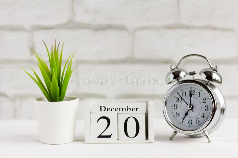 Calendar from white wooden cubes and an alarm clock on the table 20 December on yard royalty free stock photos