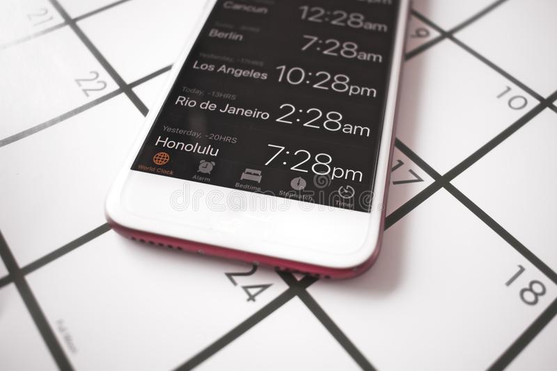 A calendar and a world time app on a mobile phone are used for travel planning to different time zones royalty free stock image
