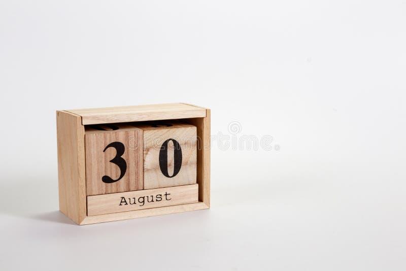 Calendario 30 agosto di legno su un fondo bianco fotografia stock