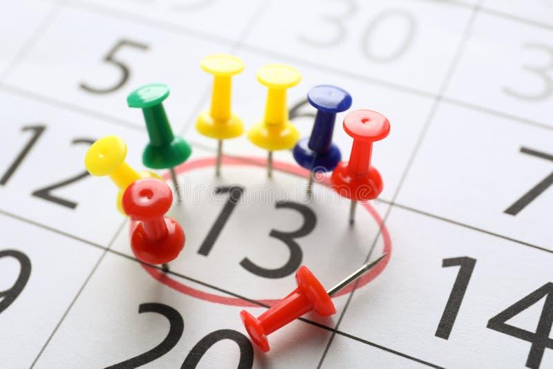 Calendario con el recordatorio y los pernos, primer de la fecha Concepto del plazo imagen de archivo