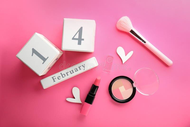 Calendario con la fecha del 14 de febrero y de cosméticos decorativos en fondo del color fotografía de archivo libre de regalías