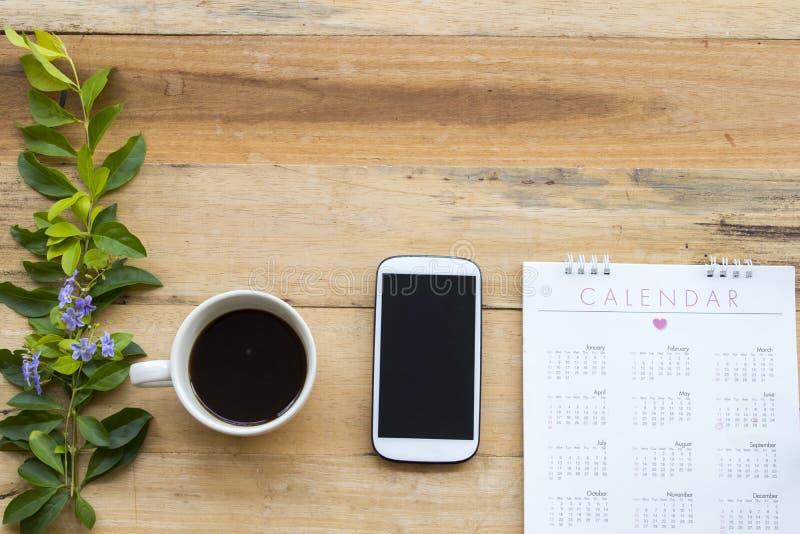 Calendario con la oficina del teléfono móvil para el trabajo del negocio fotografía de archivo libre de regalías