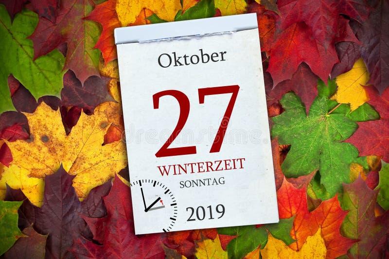 Calendario con las hojas del autum y las palabras alemanas para el cambio del invierno y del tiempo con vuelta a la hora estándar fotografía de archivo libre de regalías