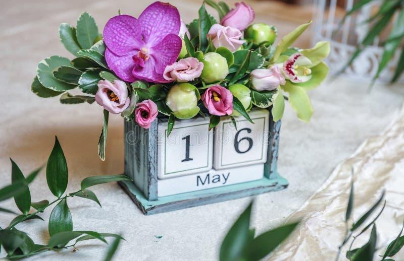 Calendario da tavolino d'annata decorato con i fiori colorati Decorazione della data di nozze fotografia stock libera da diritti