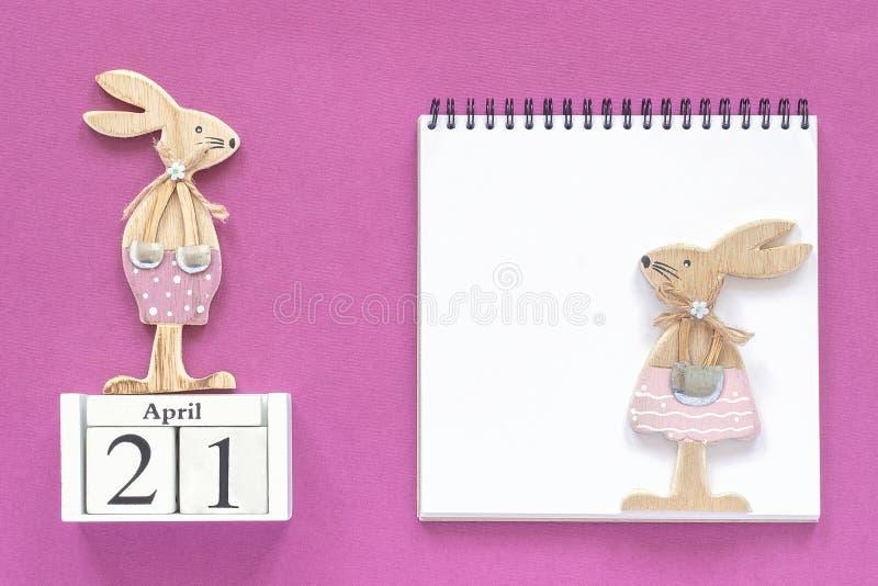 Calendario 21 de abril y pares de conejitos de pascua de madera, libreta blanca en fondo de papel púrpura Maqueta católica de Pas fotografía de archivo
