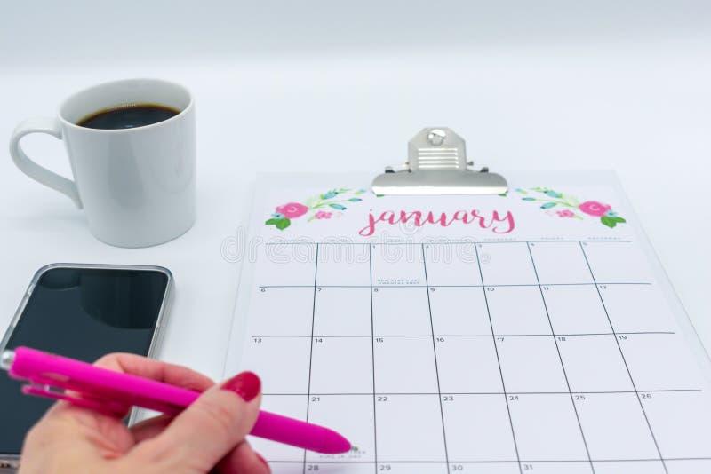 Calendario de enero con la mano y la taza de café de la mujer fotos de archivo
