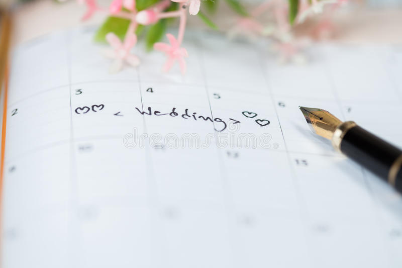 Calendario de la boda en la tabla foto de archivo libre de regalías