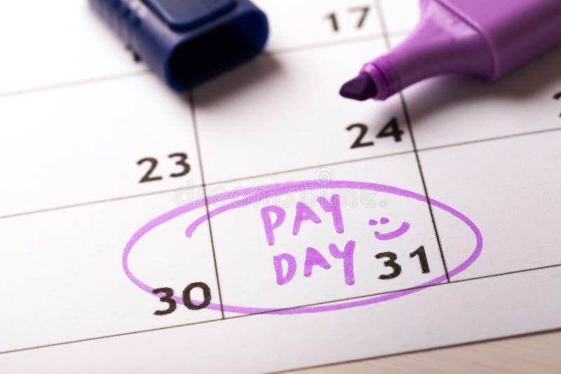Calendario del concepto del día de paga con el marcador y el día circundado de sueldo imágenes de archivo libres de regalías