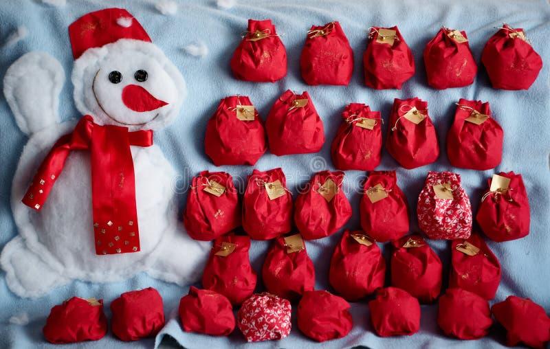 Calendario di avvenimento Pupazzo di neve e sacchetti rossi del panno fotografie stock libere da diritti