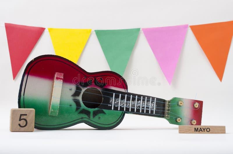 Calendario di legno del cubo con la data di Cinco de Mayo, la chitarra del giocattolo e le bandiere variopinte