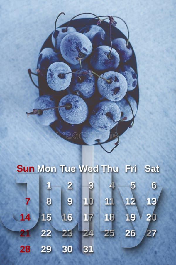 Calendario di luglio Pila di ciliegie congelate con il calendario di mese di luglio Estate immagine stock